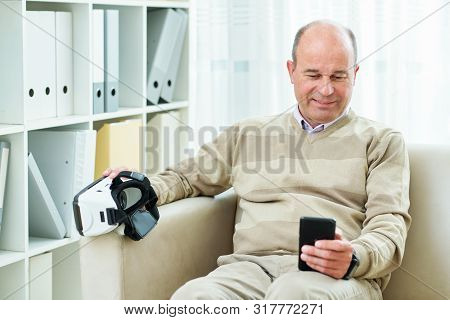 Smiling Mature Man Sitting On Sofa And Watching Tutorial On Smartphone Before Using Virtual Reality