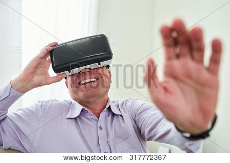 Laughing Mature Man Enjoying Playing Videogame In Virtual Reality Goggles At Home