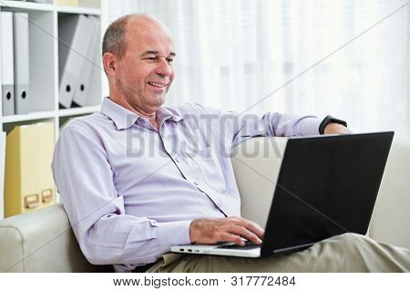 Cheerful Mature Business Executive Resting On Sofa And Reading E-mails From Clients And Coworkers On