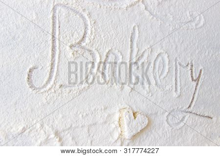 The Word Bakery Hand Written In Flour On A Wood Table. Heart Shaped Cake Covered With Flour And Suga