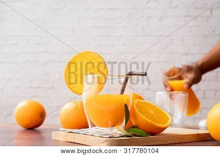 Glasses Of Freshly Squeezed Orange Juice With Human Hand Pouring Orange Juice, No Added Sugar.