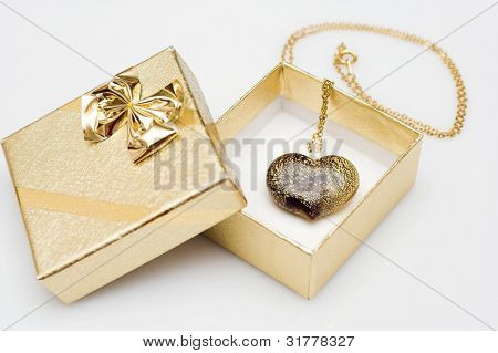 close up of little present box with heart shape pendant