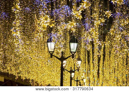 Christmas And New Year Holidays Illumination Outdoor In City Street At Night. Golden Shimmering And