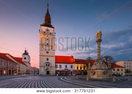 Trnava, Slovakia - April 9, 2019: City Tower And Holy Trinity Statue In The Main Square Of Trnava, S