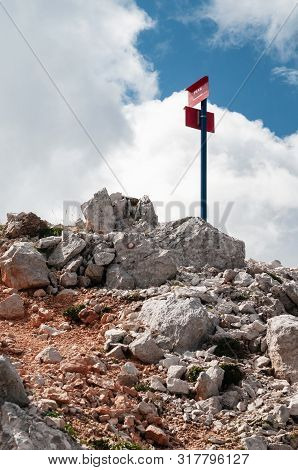 Signpost On Mountain Trail Designating The Direction And Duration To Mountain Peak And Marking On Th