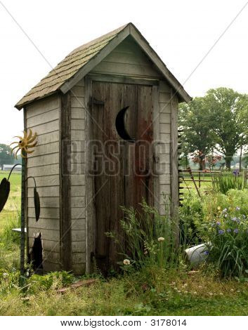 old wooden outhouse in a garden with crescent moon on the door poster
