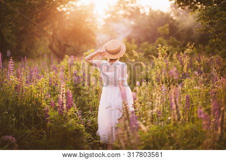 Woman From Back Holding A Basket With Lupines. Provence