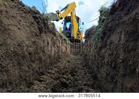 A Yellow Excavator Digging A Trench On The Construction Site, A Close-up, Against The Sky.