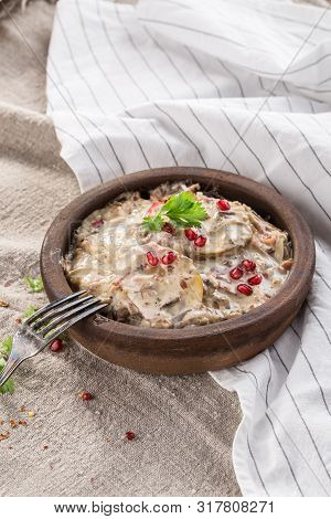 Potato Halves With White Sauce, Bacon And Mushrooms In Clay Pot On Tablecloth Side View