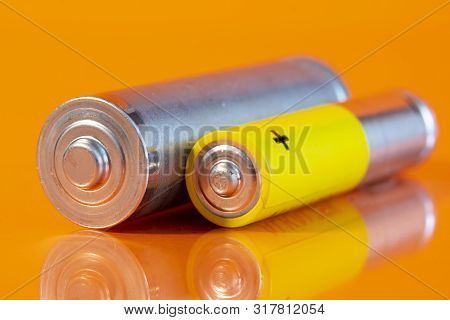 Single Used Aa And Single Aaa Alkaline Battery Are Seen On A Reflective Orange Surface. Closeup Side