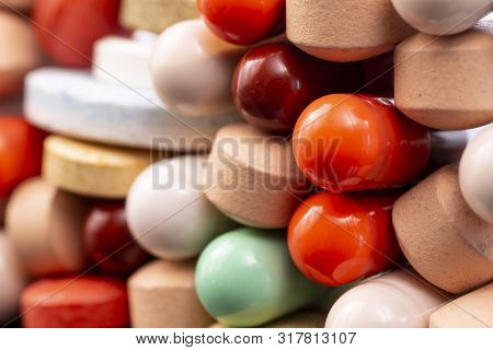 Different Colorful Pills And Capsules Stacked. Global Pharmaceutical Industry For Billions Dollars P