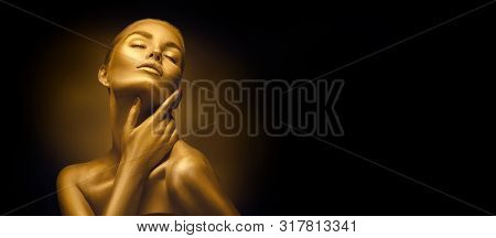 Fashion art Golden skin Woman face portrait closeup. Model girl with holiday golden Glamour shiny professional makeup. Gold jewellery, jewelry, accessories. Beauty gold metallic body, Lips and Skin