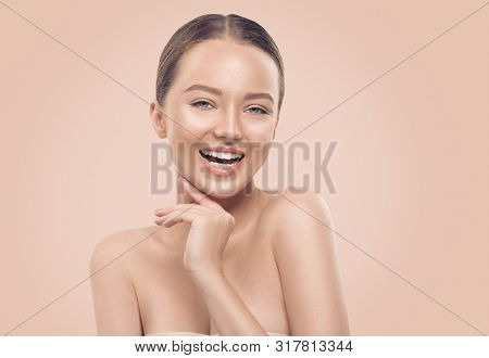 Beauty smiling young Woman with perfect fresh skin Portrait. Beautiful Spa Girl Proposing a product on beige background. Cleansing, skin care, body care concept. Skincare treatment, fresh clean skin