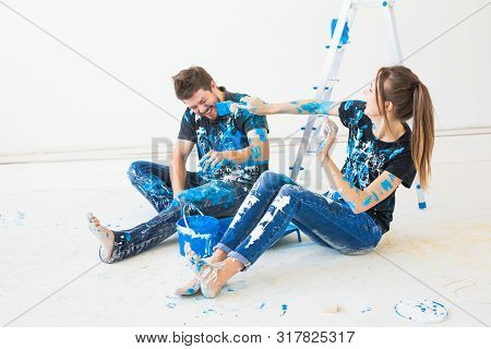 Renovation, Redecoration And People Concept - Young Couple Doing A Renovation In New Home And Have F