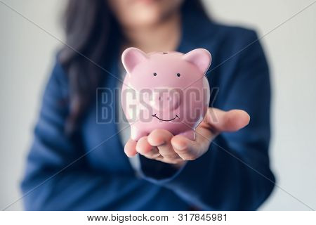 Business Woman Investor Holding Piggy Bank For Money Savings On Her Hands, Asian Businesswoman In Un