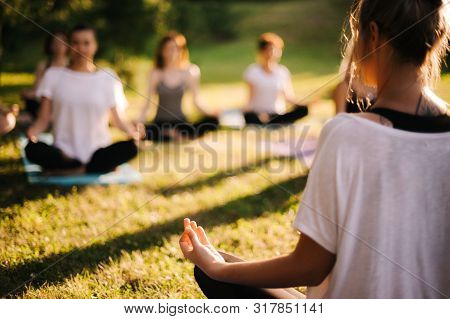 Group Of Young Sporty Woman Practicing Yoga Lesson With Instructor, Sitting In Lotus Pose. Focus Of