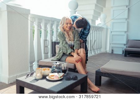 Husband Hugging His Wife While Having Breakfast Outside