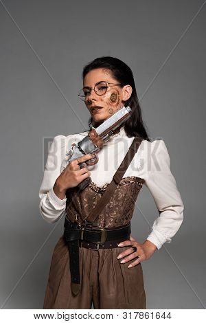 Attractive Steampunk Woman Standing With Hand On Hip And Holding Pistol Isolated On Grey