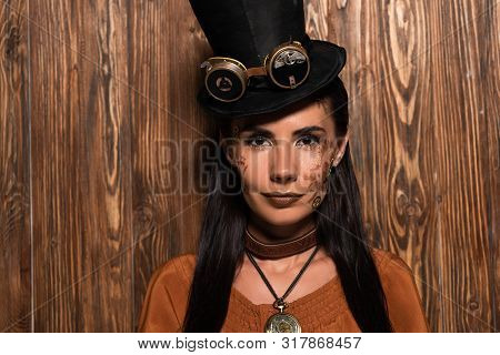 Front View Of Steampunk Woman In Top Hat With Goggles Looking At Camera On Wooden