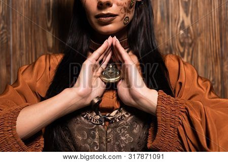 Cropped View Of Woman With Steampunk Makeup Touching Medallion On Wooden