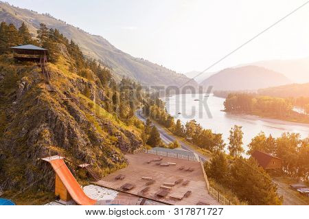 Outdoor Pool In The Mountains With A Yellow Water Slide Attraction With Wooden Chaise-longue, Blue W