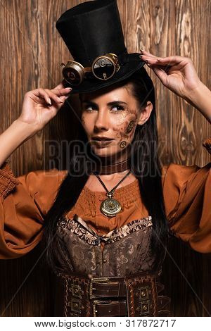Attractive Steampunk Woman Touching Top Hat With Goggles On Wooden