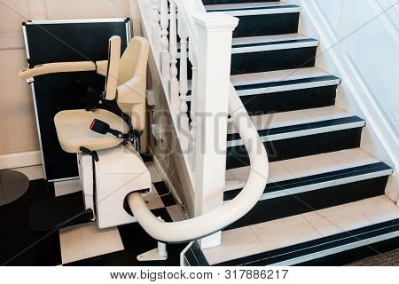 White Stairlift On Staircase For Disabled People And Elderly People Indoor In Home Or School And Off