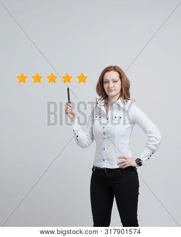 5 star rating or ranking, benchmarking concept on grey background. Woman assesses service, hotel or restaurant