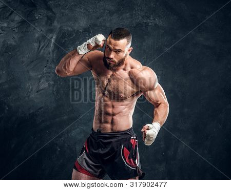 Manly Bearded Man With Beautiful Muscular Torso Is Posing For Photographer On The Dark Background.