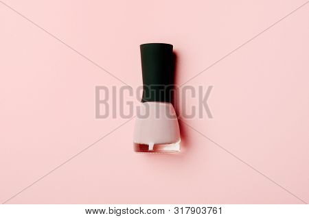 Nail polish bottle on stylish pink background. Pink fingernail varnish with black cap. Female cosmetics accessory. Manicure enamel, pedicure lacquer top view on nude backdrop. Minimalist promo banner poster