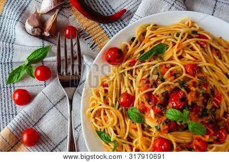 Italian Spaghetti With Tomato Sauce. Cherry Tomatoes And Basil On A White Dish On A Linen Tablecloth