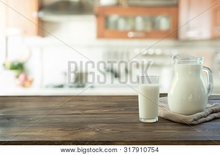 Glass of fresh milk and jug on wooden tabletop with blur kitchen as background. poster