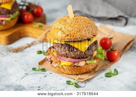 A Set Of Homemade Delicious Burgers Of Beef, Bacon, Cheese, Lettuce And Tomatoes On A Light Concrete