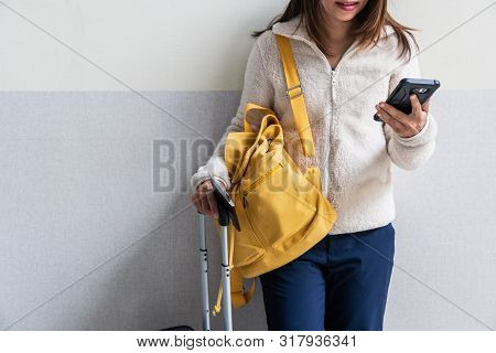 Young Woman Traveler With Baggage And Backpack Using Smartphone At The Airport