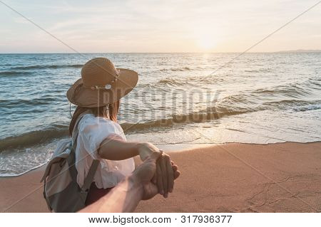 Young Woman Traveler Holding Man's Hand And Looking Beautiful Sunset On The Beach, Couple Vacation T