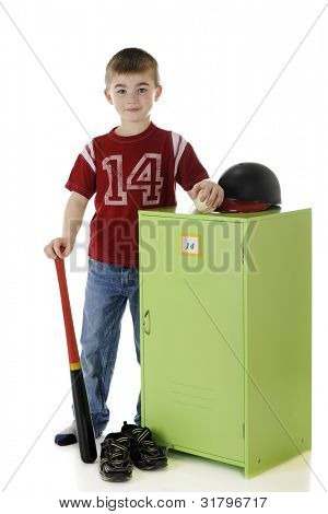 Full length portrait of a young elementary baseball player standing by his locker with his gear.  On a white background.