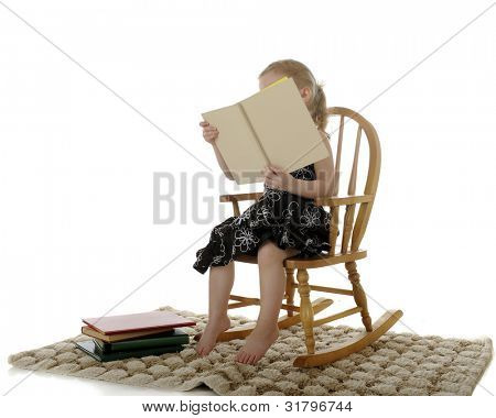 An adorable preschooler reading with her book covering her face.  She sits in a child's rocker on a tan rug with other books nearby.  On a white background.