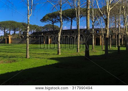 Pompeii, Italy Palestra Grande courtyard. Large central space for gymnastic exercises, Palestra of Gymnasium, with background view of stone built 20.000 capacity Roman Anfiteatro di Pompeii. poster