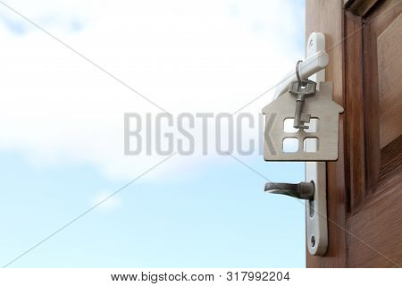 Open Door To The Street With A Key And A Key Fob In The Shape Of A House Symbol With A View Of The C