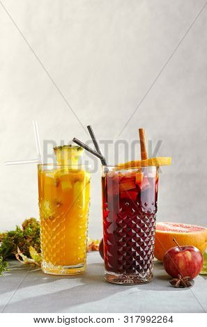 Set of hot autumn cocktails with red and white spicy mulled wines. Apple cinnamon spiced fall mulled wine and warm tropical gluhwein with pineapple and orange in transparent glass cups on grey table