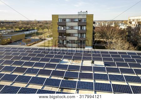 Aerial view of blue shiny solar photo voltaic panels system on commercial roof producing renewable clean energy on city landscape background. poster
