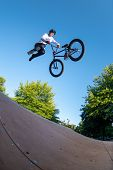Bmx stunt performed at the top of a mini ramp on a skatepark. poster