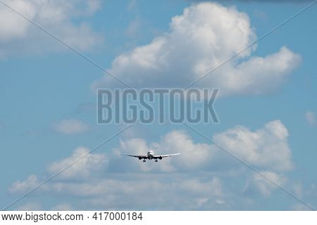 The Plane, Painted In A White Livery, Comes In To Land Against The Background Of Clouds In The Sky.