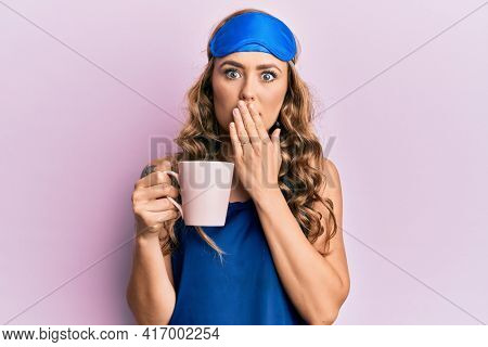 Young blonde girl wearing sleep mask and pyjama drinking coffee covering mouth with hand, shocked and afraid for mistake. surprised expression