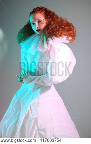 Redhead female model with lush curly hair posing in a white art dress on grey background. A studio portrait with green and red color lighting. Fashion art.