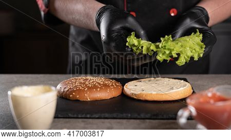 Step By Step Recipe. Stage 3. The Chef Prepares A Delicious Burger. Close-up Of A Hand In Black Glov