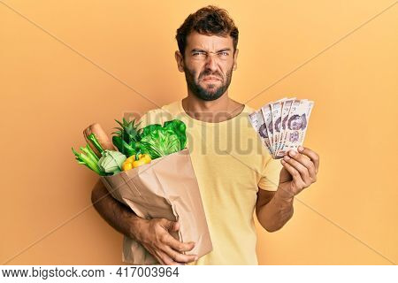Handsome man with beard holding groceries and 500 mexican pesos banknotes skeptic and nervous, frowning upset because of problem. negative person.
