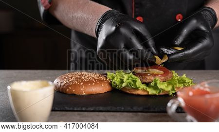 Step By Step Recipe. Stage 6. The Chef Prepares A Delicious Burger. Close-up Of A Hand In Black Glov