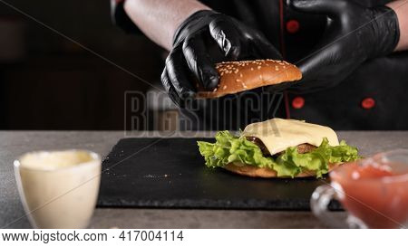 Step By Step Recipe. Stage 8. The Chef Prepares A Delicious Burger. Close-up Of Hands In Black Glove
