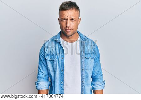 Handsome muscle man wearing casual denim jacket skeptic and nervous, frowning upset because of problem. negative person.